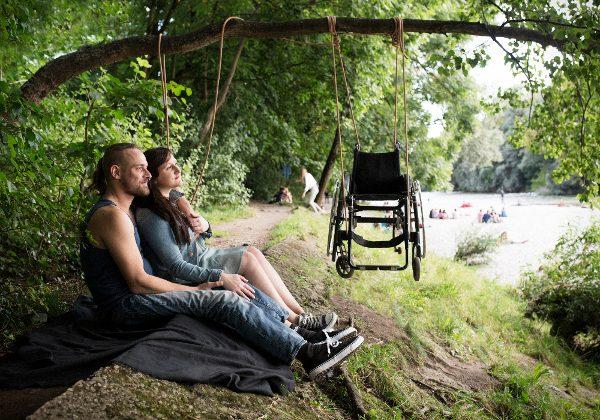 junger Mann und junge Frau in der Natur sitzend, über Ihnen ein Rollstuhl, der an einer Schnur an einem Ast hängt