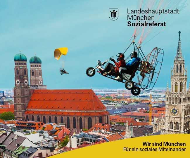 Zwei Menschen mit Motorradhelm sitzen in einem offenen Mobil, das über die Münchner Innenstadt fliegt. Im Hintergrund ist der Turm des Münchner Rathauses und die Frauenkirche zu sehen.