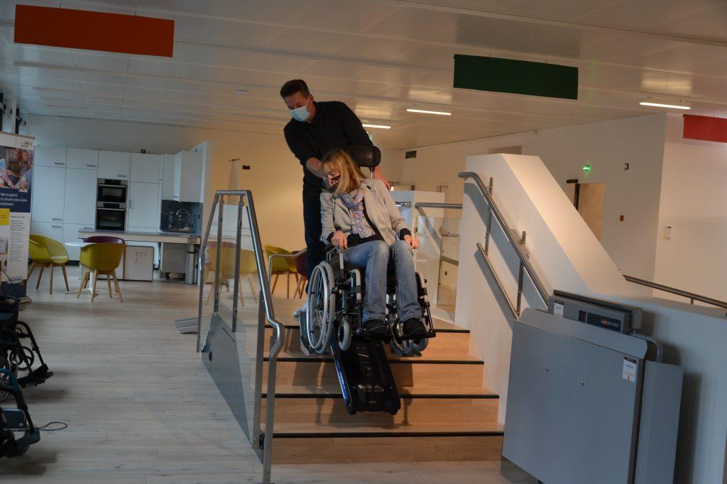 Ein Mann zieht einen Rollstuhl, in dem eine Frau sitzt, die Treppen hoch.