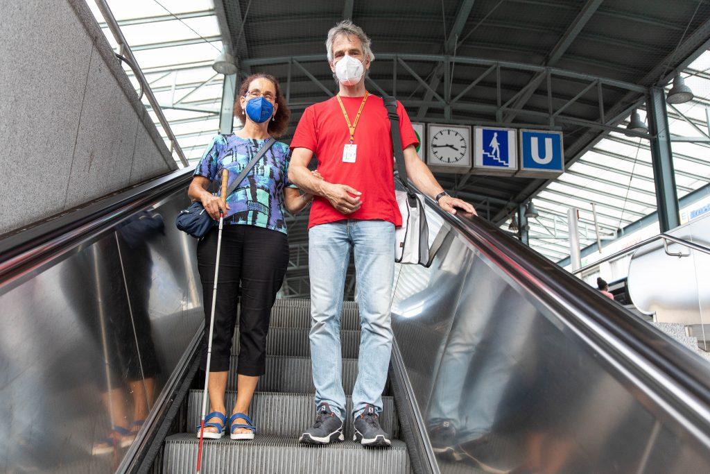 Eine Frau mit einem Langstock steht neben einem Mann auf einer Rolltreppe. Die Frau hält sich am Arm des Mannes fest.