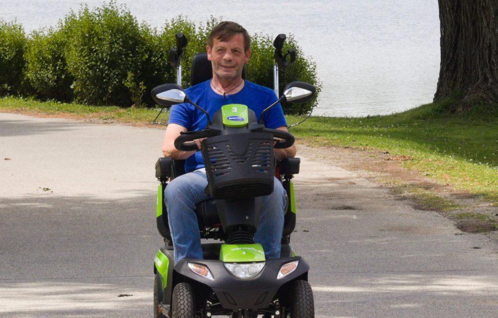 Ein Mann sitzt in einem Elektromobil.