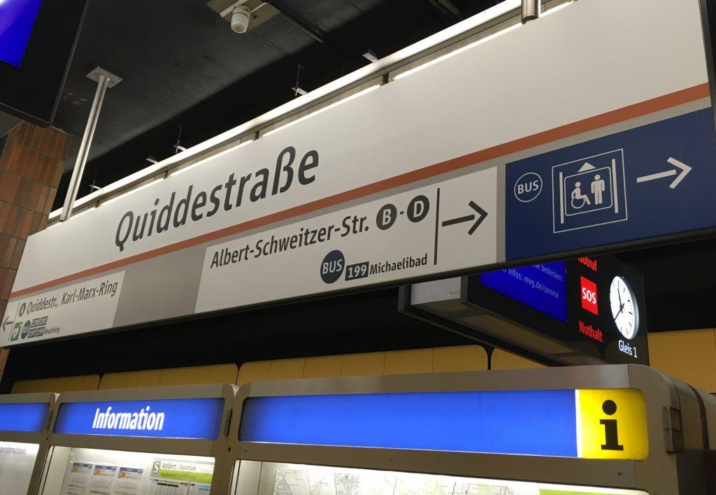 Hinweisschild in der U-Bahn-Station Quiddestraße mit großem Aufzug-Piktogramm und Bus-Symbol