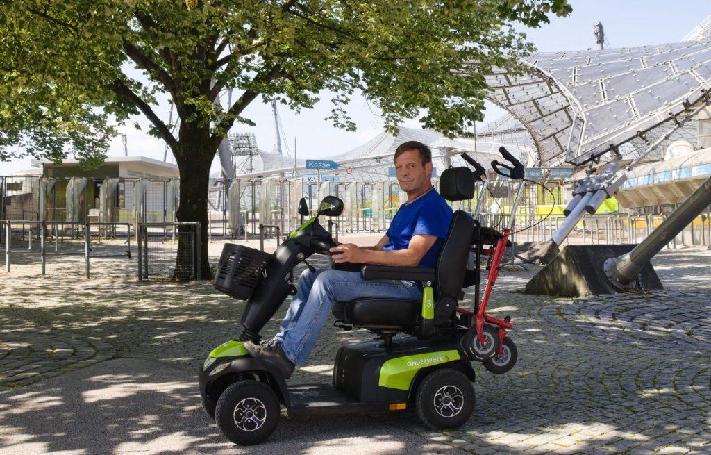 """Ein Mann sitzt in einem Elektromobil. Auf dem Elektromobil steht """"anderwerk"""". Im Hintergrund ist das Zeltdach des Olympiaparks"""