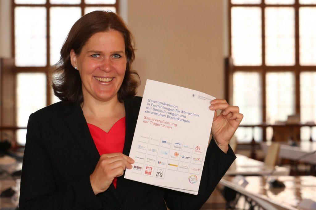 """Bürgermeisterin Verena Dietl hält folgendes Dokument in den Händen: """"Selbstverpflichtung der Träger*innen zur Gewaltprävention in Einrichtungen für Menschen mit Behinderungen und chronischen Erkrankungen"""""""