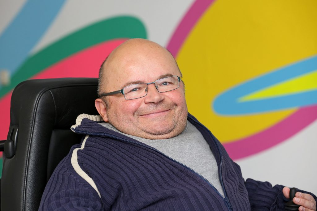 Der Behindertenbeauftragte Oswald Utz sitzt im Rollstuhl vor einer bunten Wand